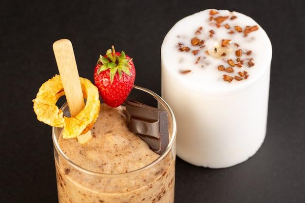 Eine ansicht des braunen schoko-desserts der vorderansicht leckeres leckeres süßes mit schokoladenpulver-schokoriegel und erdbeere lokalisiert mit weißer kerze auf dem dunklen hintergrund süßes erfrischungsdessert