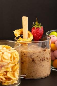 Eine ansicht des braunen schoko-desserts der vorderansicht leckeres leckeres süßes mit schokoladenpulver-schokoriegel und erdbeere mit cornflakes und bonbons auf dem dunklen hintergrund süßes erfrischungsdessert