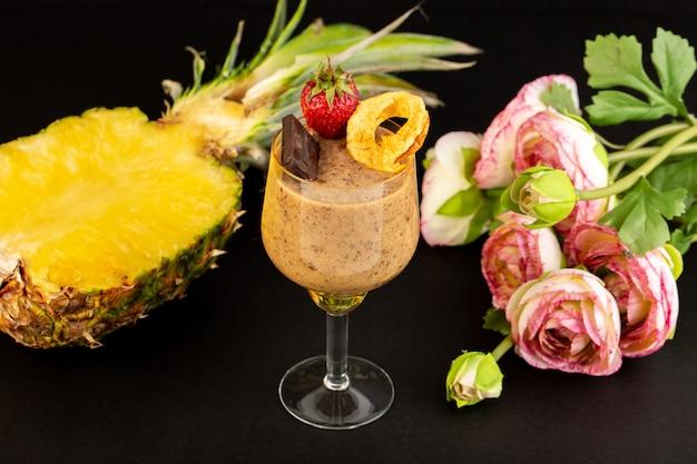 Eine ansicht des braunen schoko-desserts der vorderansicht leckeres leckeres süßes mit schokoladenpulver-schokoriegel und erdbeere mit geschnittener ananas auf dem süßen hintergrund süßes erfrischungsdessert