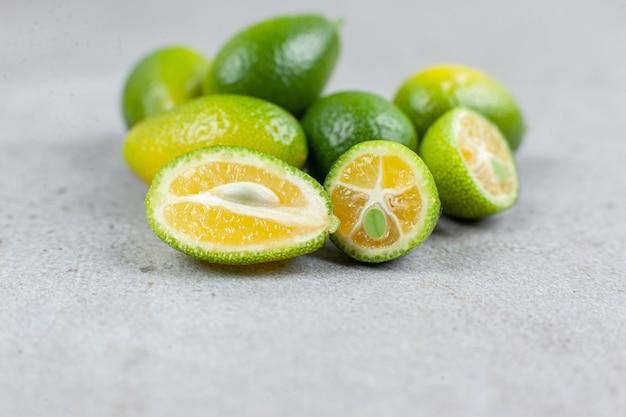 Eine anzahl von ganzen und geschnittenen kumquats auf marmorhintergrund. hochwertiges foto