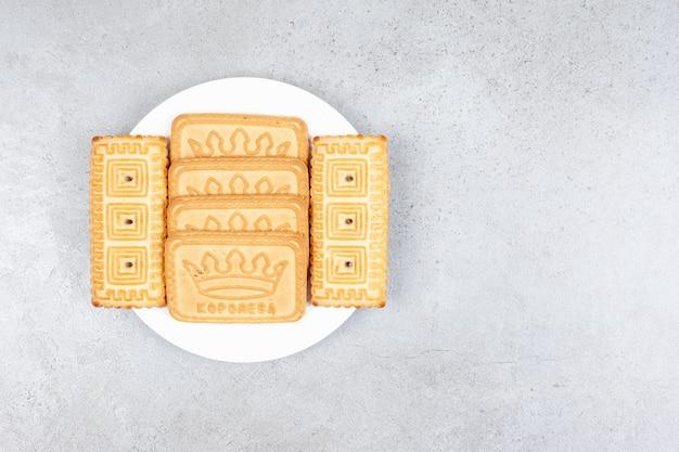 Eine anzahl von keksen, die auf einem teller auf marmorhintergrund ausgerichtet sind. hochwertiges foto