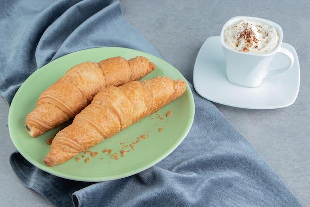 Eine anzeige des croissants im teller auf handtuch und mit kaffee, auf dem marmorhintergrund. hochwertiges foto