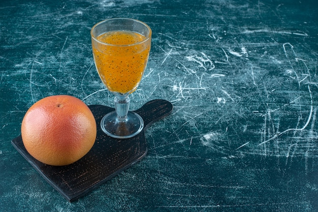 Eine anzeige eines glases des verarbeiteten saftes und der grapefruit auf dem blauen hintergrund. hochwertiges foto