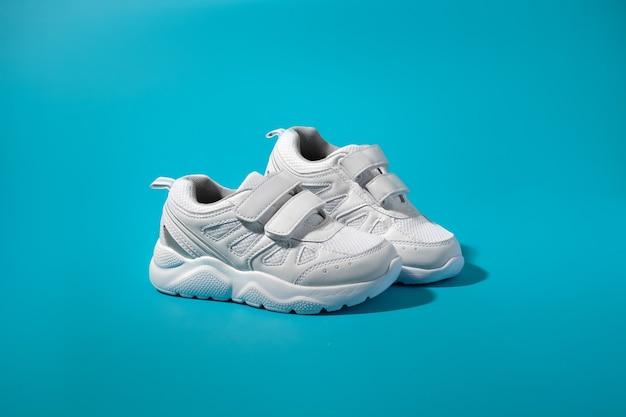 Eine anzeige für weiße teenie-sneaker, die seitlich auf einem isolierten blauen papierhintergrund mit rauer sonne stehen...