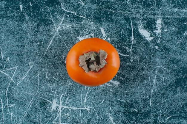 Eine anzeige reifer kaki auf dem marmortisch.