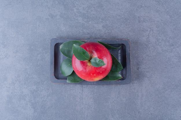 Eine anzeige von apfel auf einer holzplatte auf marmortisch.