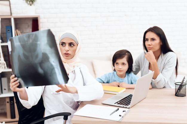 Eine arabische ärztin untersucht eine röntgenaufnahme.