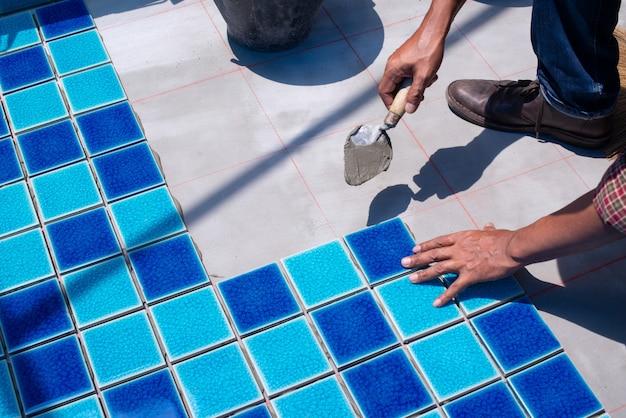 Eine arbeitskraft, die fliesen zu hause repariert, installation des fliesen auf dem kleber, mit der kelle in der hand