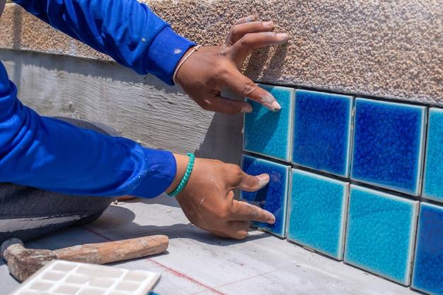 Eine arbeitskraft, die fliesen zu hause repariert, installation von fliesen auf dem kleber