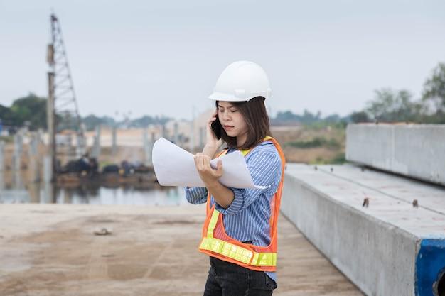 Eine architektin, die einen schutzhelm trägt, überprüft mit dem smartphone den bauplan des brückenbaus.