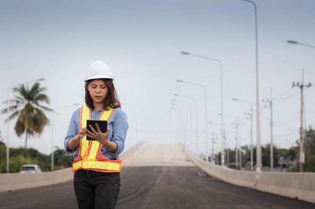 Eine architektin, die einen schutzhelm trägt, verwendet ein tablet, um den bauplan des brückenbaus zu überprüfen.