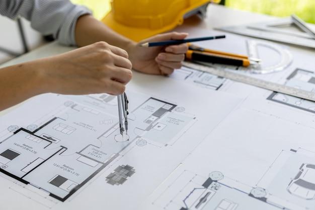 Eine architektin zeichnet mit einem karussell die hausentwürfe nach, sie prüft die von ihr entworfenen hauspläne, bevor sie sie an die kunden schickt, sie entwirft das haus und die inneneinrichtung.