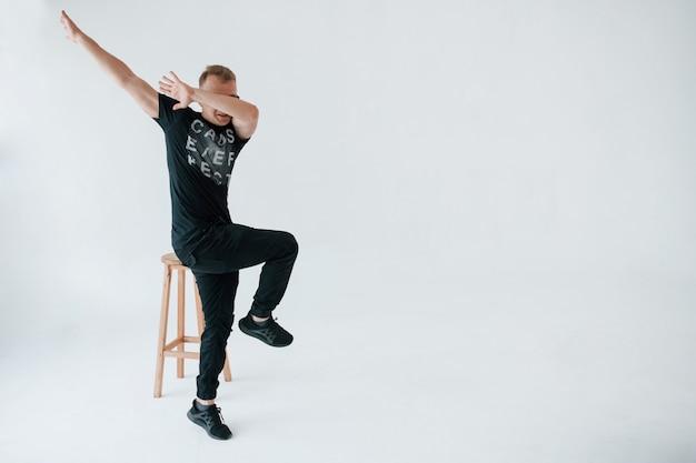 Eine art moderne meme-geste. positiver mann in freizeitkleidung hat spaß im studio gegen weiße wand