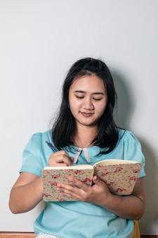 Eine asiatin denkt im urlaub über einen neuen job zu hause nach und schreibt alles, was sie denkt, zuerst in ihr notizbuch.