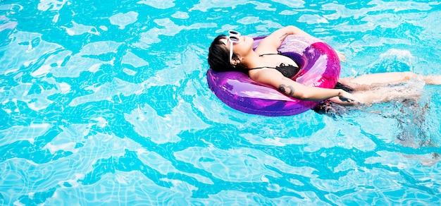 Eine asiatin, die in den swimmingpool mit aufblasbarem rohr schwimmt
