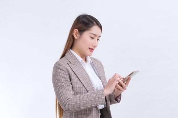 Eine asiatische berufstätige frau in einem formellen anzug in einem weißen hemd telefoniert, um informationen zu überprüfen.