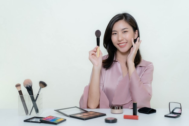 Eine asiatische bloggerin, die ein video von sich selbst mit einem orangefarbenen lippenstift in einem studio dreht.