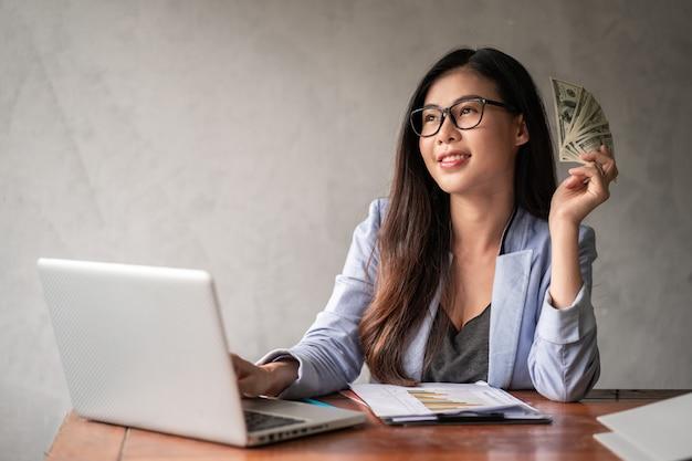 Eine asiatische frau arbeitet von zu hause aus und freut sich, dollargeld von der arbeit zu bekommen