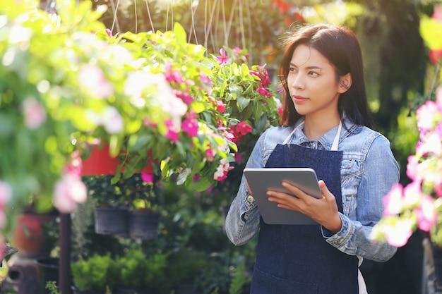 Eine asiatische frau, die ein blumengartengeschäft besitzt, zählt die blumen entsprechend der kundenbestellung.