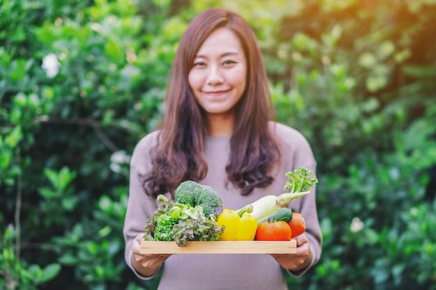 Eine asiatische frau, die ein frisches gemischtes gemüse in einem holztablett hält
