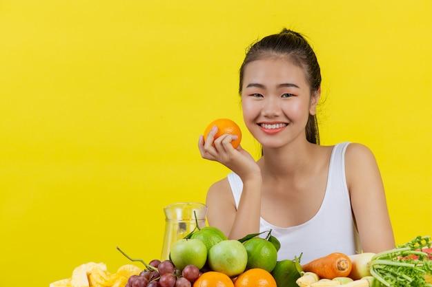 Eine asiatische frau, die ein weißes trägershirt trägt. halten sie orangen mit der rechten hand und auf dem tisch liegen viele früchte.