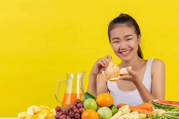 Eine asiatische frau, die ein weißes trägershirt trägt. ich schäle orangenschalen und der tisch ist voll mit verschiedenen obstsorten.