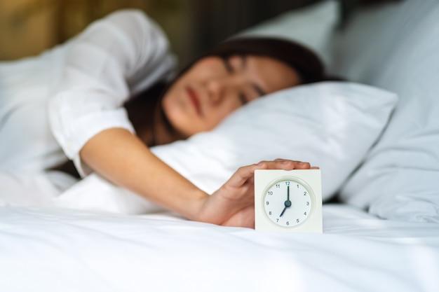 Eine asiatische frau, die einen wecker ausschaltet, während sie morgens auf einem weißen gemütlichen bett schläft