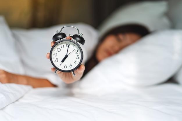 Eine asiatische frau, die einen wecker hält und zeigt, während sie morgens auf einem weißen gemütlichen bett schläft