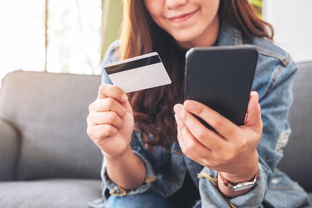 Eine asiatische frau, die kreditkarte für kauf und online-einkauf auf handy verwendet