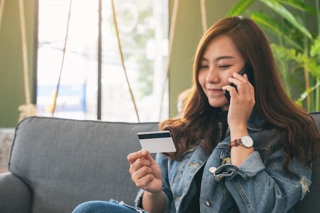 Eine asiatische frau, die kreditkarte verwendet, um online zu kaufen und einzukaufen, während sie auf mobiltelefon spricht