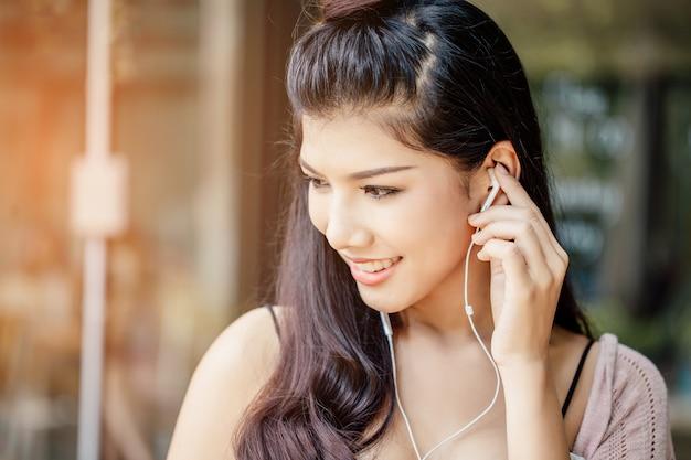Eine asiatische frau, die musik von den kopfhörern lächelt und hört.
