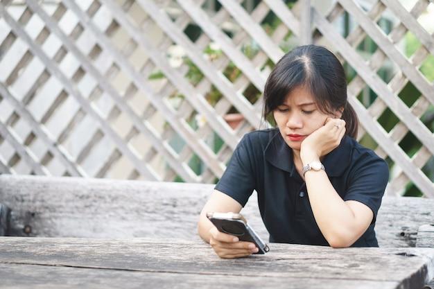 Eine asiatische frau mit ernstem ausdruck am telefon