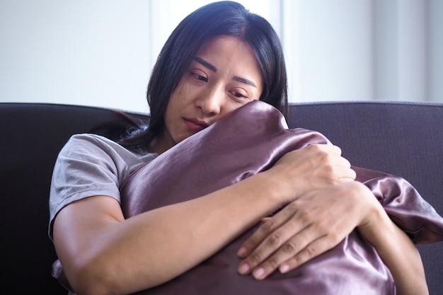Eine asiatische frau mit mentalen schmerzen sitzt alleine und umarmt ein kissen.