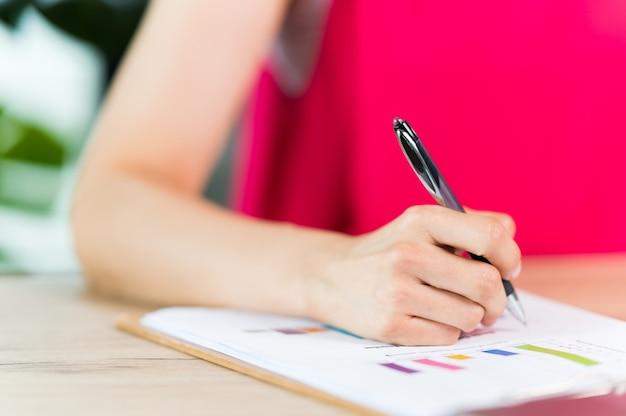 Eine asiatische frau mittleren alters, die einen vertrag unterschreibt und im büro arbeitet