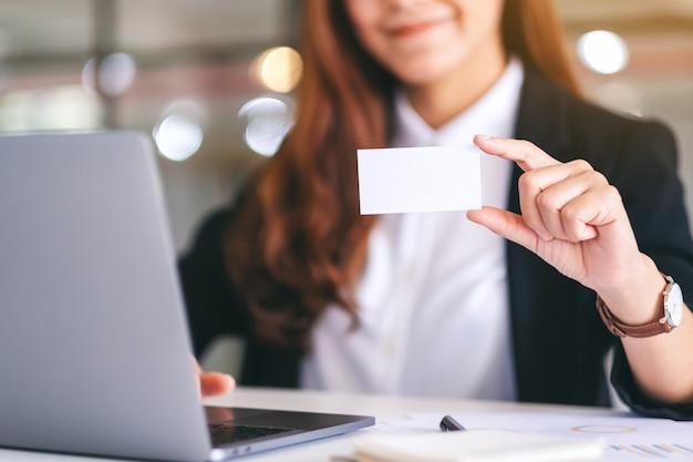 Eine asiatische geschäftsfrau, die eine leere visitenkarte hält und zeigt, während sie einen laptop im büro verwendet
