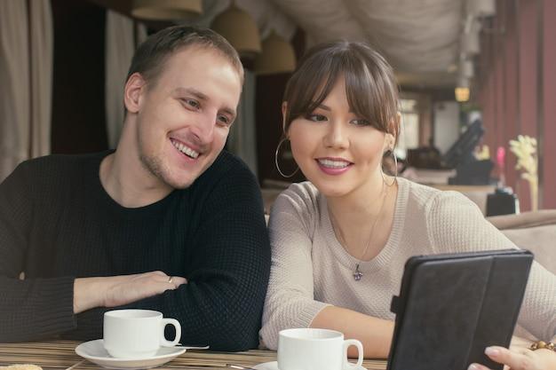 Eine asiatische junge frau und ein kaukasischer mann paaren sich im café auf einem tablet-bildschirm.