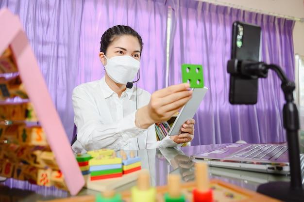 Eine asiatische lehrerin, die eine maske trägt, bringt den schülern bei, online über einen computerbildschirm zu lernen, indem sie ein online-videokonferenzsystem für die bildung verwendet