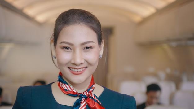 Eine asiatische schöne weibliche kabinenbesatzung lächelt an bord