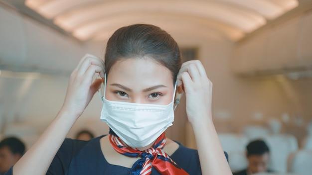 Eine asiatische schöne weibliche kabinenbesatzung trägt schutzmaske an bord, nimmt gesichtsmaske ab und lächelt