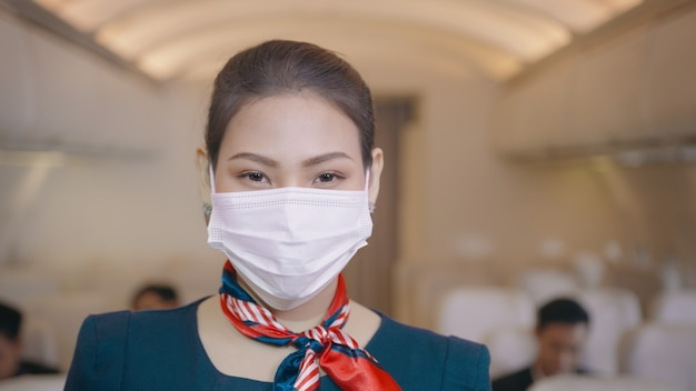 Eine asiatische schöne weibliche kabinenbesatzung trägt schutzmaske an bord