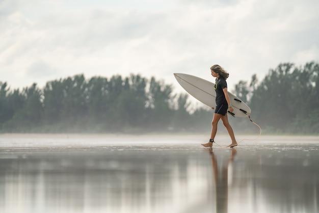 Eine asiatische sexy junge frau, die auf strand mit surfbrett in phuket geht