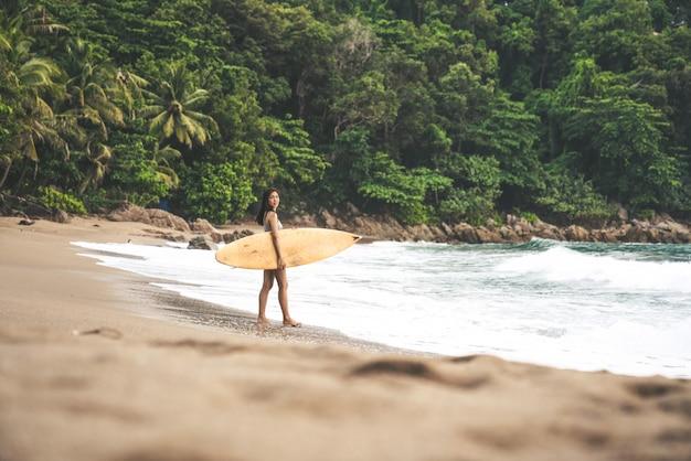 Eine asiatische sexy junge frau, die auf strand mit surfbrett in phuket thailand geht