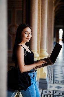 Eine asiatische studentin, die auf dem campus an ihrem laptop arbeitet