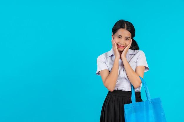 Eine asiatische studentin, die eine stofftasche spinnt und verschiedene gesten auf einem blau zeigt.