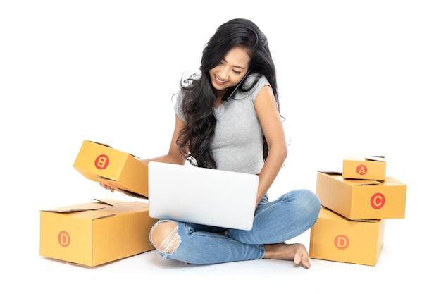 Eine asiatische unternehmerin am telefon, die die waren auf seinem computer untersucht
