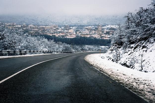 Eine asphaltstraße zwischen den schneebedeckten hügeln, die mit vegetation bedeckt sind, führt in das tal des bergkurortdorfes sukko in russland.