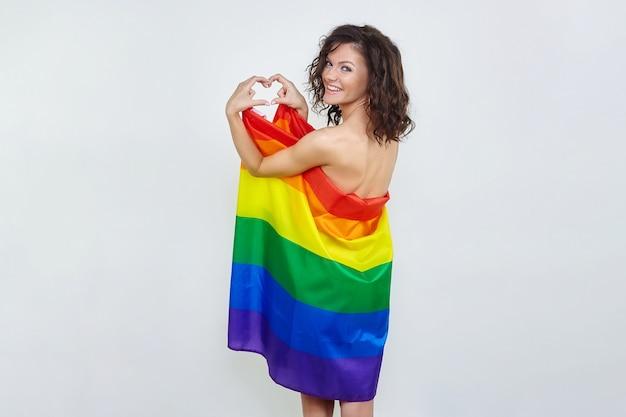Eine attraktive brünette mit einer lgbt-flagge faltete ihre hände in form eines herzens