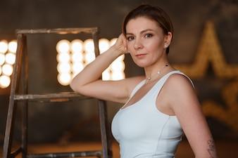 Eine attraktive Brunettefrau, die in einer Innenarchitektur eines Raumdachbodens mit Retro- Birnenlichtstandplatz aufwirft