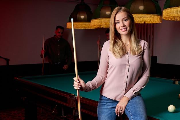 Eine attraktive dame kam, um mit freunden billard oder snooker zu spielen, während sie auf einem grünen billardtisch saß