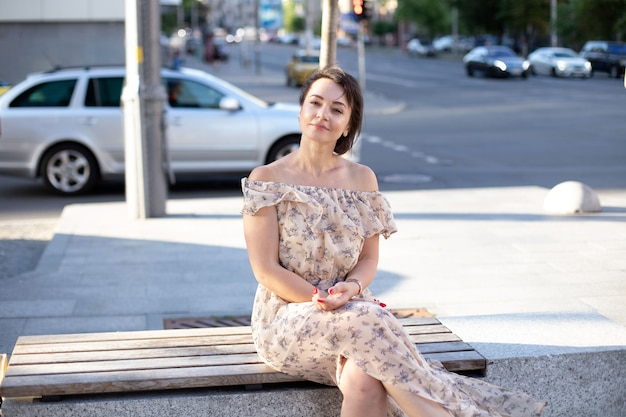 Eine attraktive erwachsene frau in einem kleid sitzt auf einer bank mitten in einer städtischen straße vor dem hintergrund einer ampel und einer straße. welttourismustag